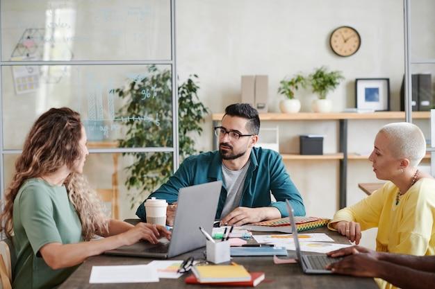 Líder empresarial masculino sentado à mesa e conversando com seus funcionários durante uma reunião de negócios no escritório