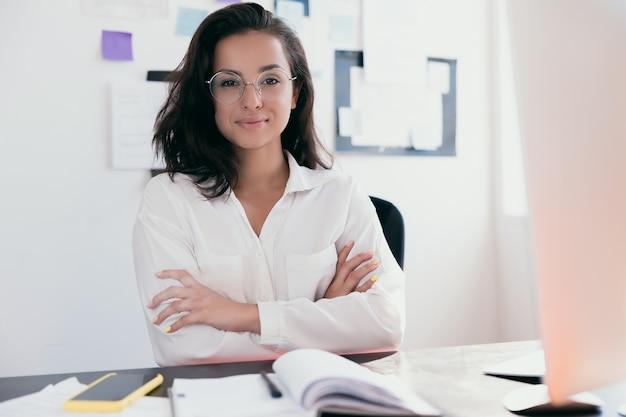 Líder feminina confiante e bem-sucedida, de braços cruzados e olhando para a câmera com um sorriso