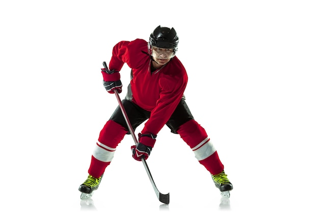 Líder. jogador de hóquei masculino com o taco na quadra de gelo e parede branca. desportista usando equipamento e praticando capacete. conceito de esporte, estilo de vida saudável, movimento, movimento, ação.