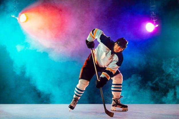 Líder. jogador de hóquei masculino na quadra de gelo e fundo colorido de néon escuro com lanternas e fumaça. desportista na prática de equipamentos. conceito de esporte, estilo de vida saudável, movimento, bem-estar, ação.