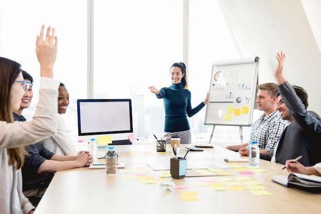 Líder jovem empresária asiática casual pedindo opinião na reunião