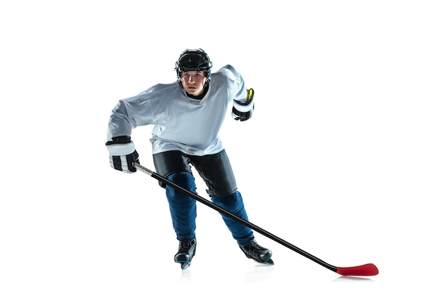 Líder. jovem jogador de hóquei com o taco na quadra de gelo e fundo branco. desportista usando equipamento e treino de capacete. conceito de esporte, estilo de vida saudável, movimento, movimento, ação.