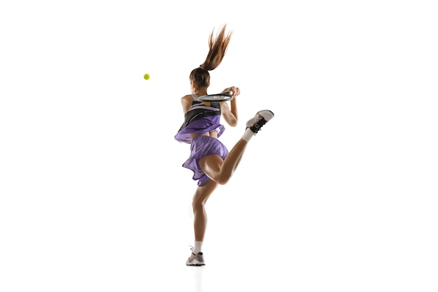 Líder. jovem mulher caucasiana jogando tênis conceito isolado, ação e movimento. apto treinamento de esportista profissional, praticando.