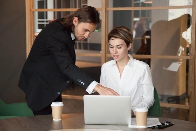 Líder masculino ajudando parceiro ajudando com inicialização on-line
