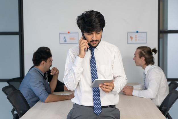 Líder novo focalizado que verifica dados com o telefone e a tabuleta na reunião de negócios.