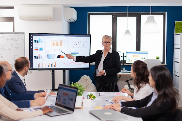 Líder sênior da empresa em debate na sala de conferências equipe corporativa discutindo novo aplicativo de negócios com colegas olhando para a tela