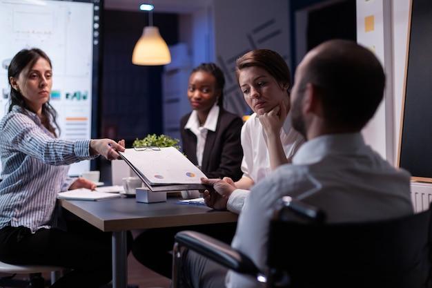Líder viciado em trabalho em cadeira de rodas discutindo estatísticas de gerenciamento resolvendo gráficos da empresa