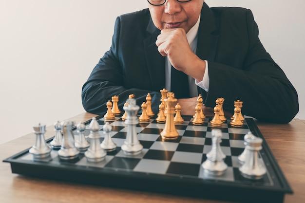 Liderança de empresário jogando xadrez, pensando o plano de estratégia sobre o acidente derrubar o time oposto