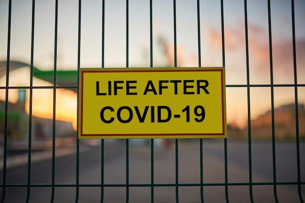 Life after covid-19 assina em cima do muro com vista da cidade de blured ao pôr do sol