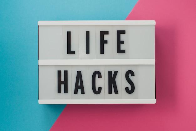 Life hacks - texto em uma tela na superfície brilhante azul e rosa.