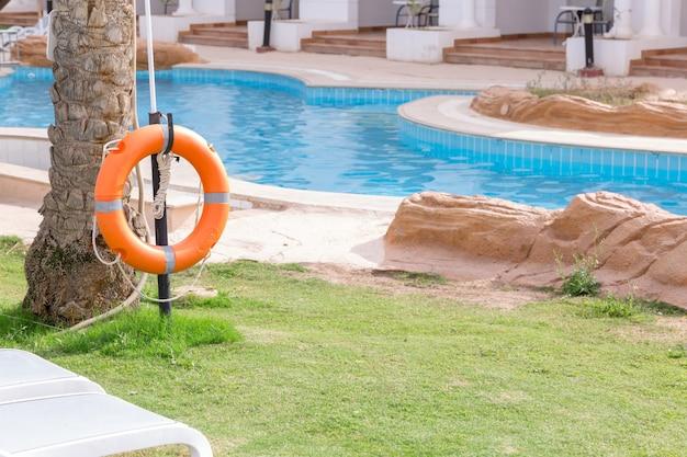 Lifebuoy em cima do muro, à beira da piscina de férias no hotel