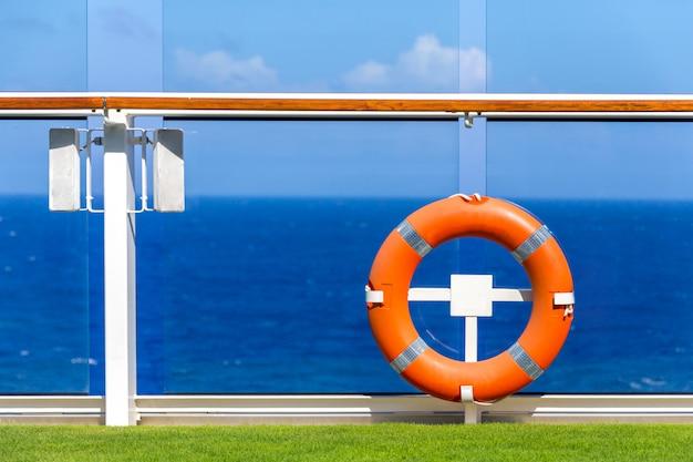 Lifebuoy laranja em um convés de navio de cruzeiro com o oceano no fundo com espaço de céu azul e cópia