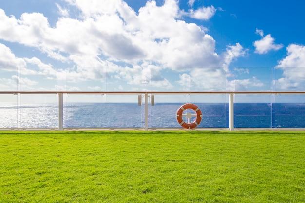 Lifebuoy laranja em um convés de navio de cruzeiro com oceano no fundo com céu azul e espaço de cópia