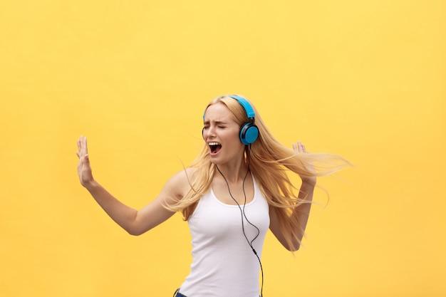 Lifestyle concept: retrato de uma mulher alegre em t-shirt branca e ouvir música