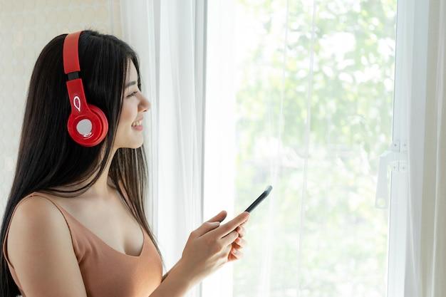 Lifestyle linda mulher asiática linda garota se sentir feliz desfrutar de ouvir música com fones de ouvido fones de ouvido no quarto branco