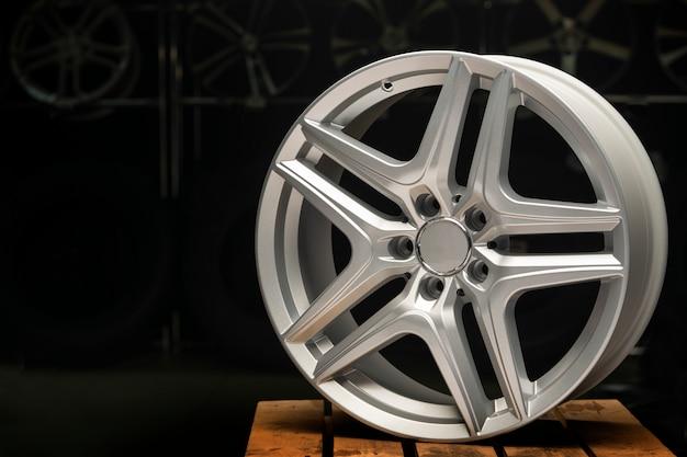 Liga a prata da roda, borda a roda de carro nova em um fim preto acima.