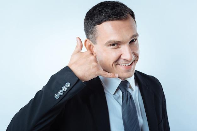 Liga para mim. homem bonito, alegre e simpático sorrindo e olhando para você enquanto mostra um gesto de chamada com a mão