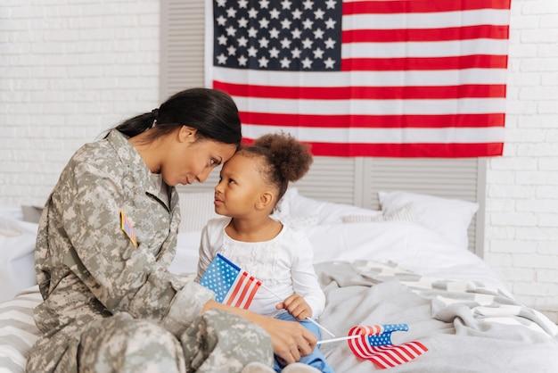Ligação forte. mãe forte e apaixonada e carinhosa e sua filha sentadas juntas em uma cama e olhando nos olhos uma da outra enquanto passam seu tempo livre juntas