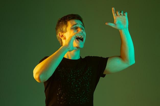 Ligando para alguém, gritando. retrato do homem caucasiano isolado no fundo verde do estúdio em luz de néon. lindo modelo masculino de camisa preta. conceito de emoções humanas, expressão facial, vendas, anúncio.