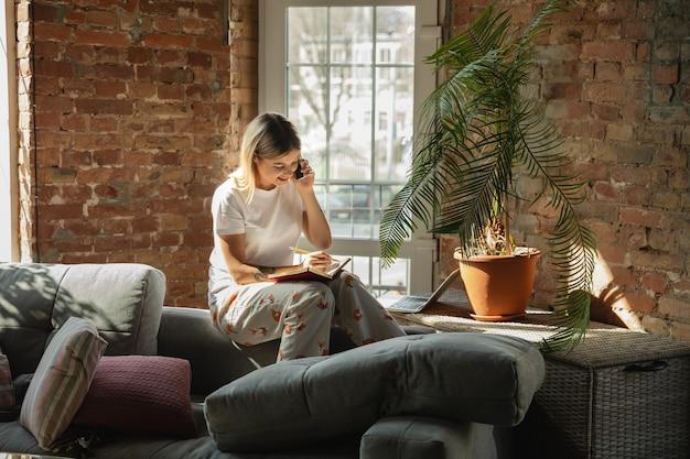 Ligando para clientes. mulher caucasiana, freelancer durante o trabalho em home office durante a quarentena. jovem empresária em casa, auto-isolada. usando gadgets. trabalho remoto, prevenção de disseminação de coronavírus.