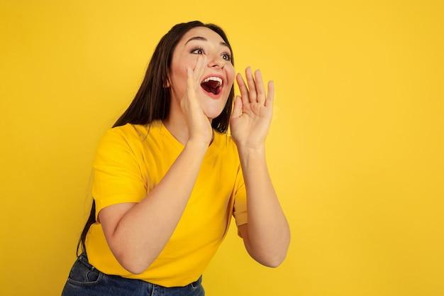 Ligando para vendas. retrato da mulher caucasiana isolado no fundo amarelo do estúdio. bela modelo moreno feminino em estilo casual. conceito de emoções humanas, expressão facial, anúncio, copyspace.
