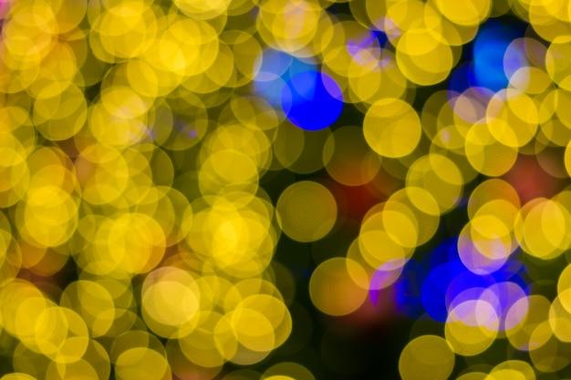 Ligas desfocadas de fundo de árvore de natal dourada