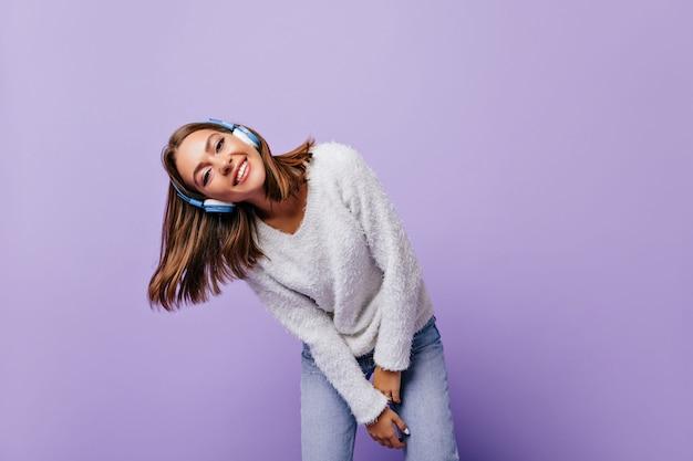 Ligeira jovem se inclinando, posando relaxada e sorrindo amigável. retrato de aluna em fones de ouvido azuis modernos