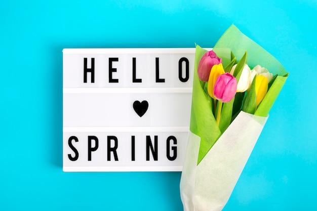 Lightbox com citação olá primavera, tulipas coloridas sobre fundo azul.