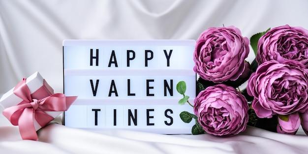 Lightbox com o texto happy valentines bouquet de lindas peônias violetas sobre fundo de tecido de seda branca. copie o espaço. cartão de felicitações. dia dos namorados
