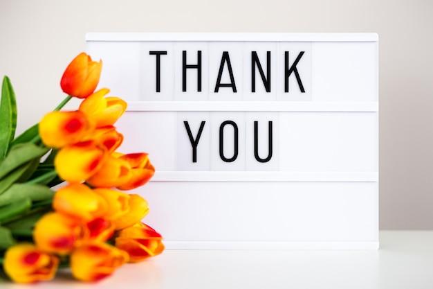Lightbox com o texto obrigado e flores de tulipa na mesa