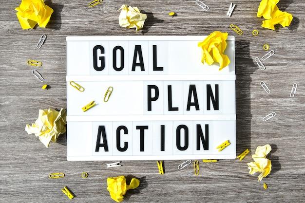 Lightbox com texto goal plan action em madeira