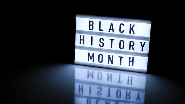Lightbox com texto mês de história preto em fundo preto escuro com reflexo no espelho. evento histórico da mensagem. luz