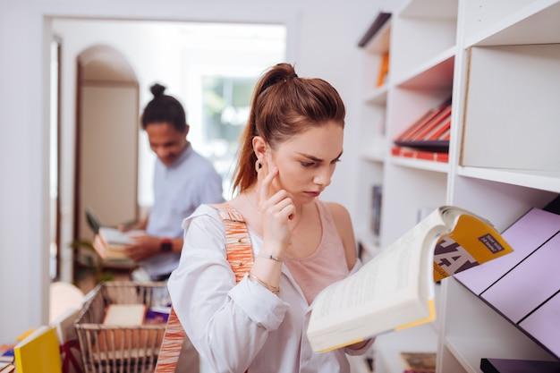 Ligue a imaginação. mulher jovem e séria franzindo a testa enquanto lê um livro