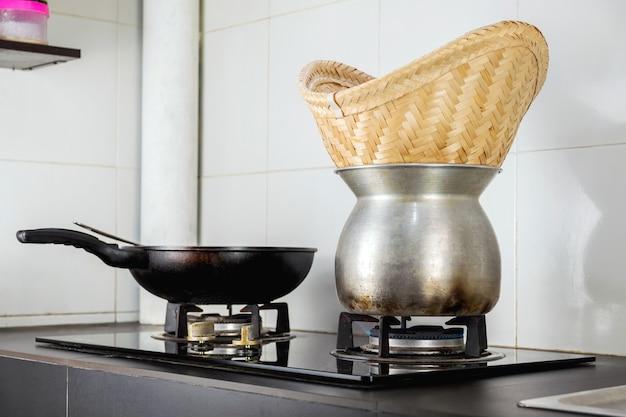 Ligue o fogão a gás para cozinhar o arroz pegajoso e cozinhe na cozinha