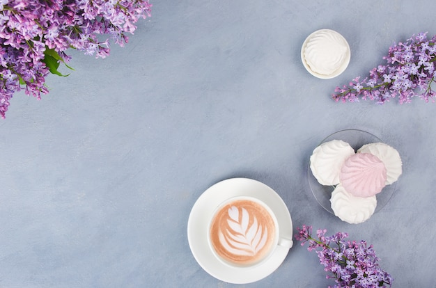 Lilás, café com latte art e marshmallow na mesa de madeira cinza. manhã romântica. configuração plana