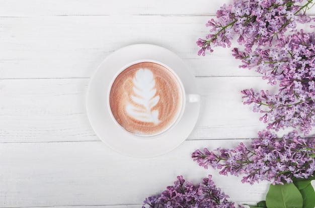 Lilás, café com latte art na mesa de madeira clara. manhã romântica. plano plano