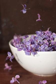 Lilás roxo brilhante em uma tigela em cima da mesa.