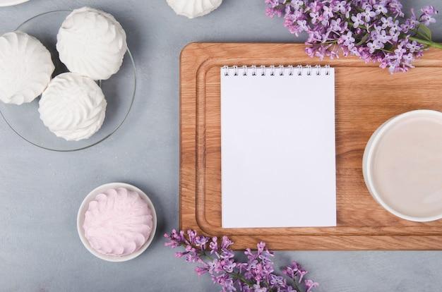Lilás, xícara de café com latte art e marshmallow na mesa de madeira branca