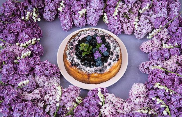 Lilases e lírios do vale são forrados com uma moldura e um bolo com mirtilos