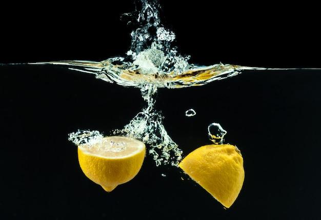 Limão amarelo fresco em respingos de água em preto