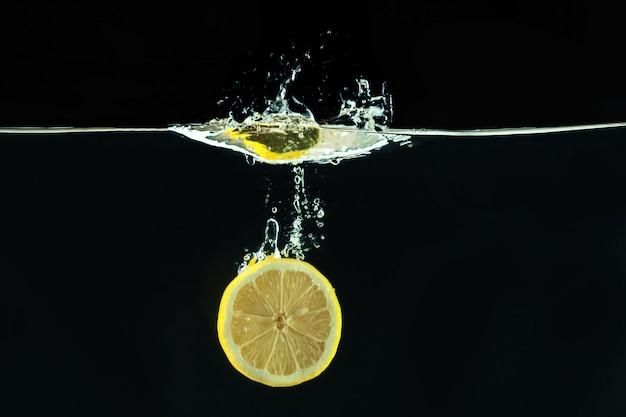 Limão amarelo fresco em respingos de água no fundo preto