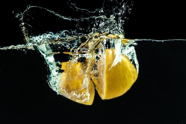 Limão amarelo fresco em respingos de água