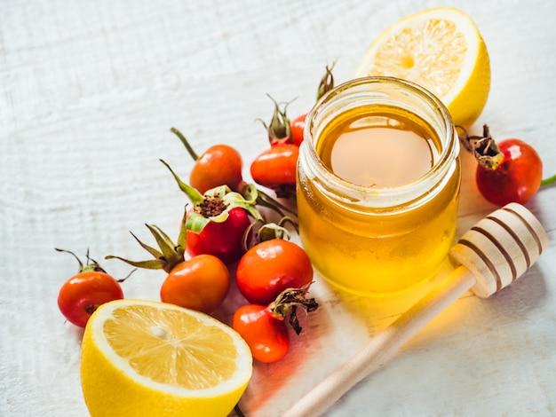Limão amarelo fresco, jarro de mel e bagas vermelhas
