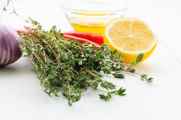 Limão amarelo metade, verde pimenta de ramo de thyne, azeite, cabeça de alho