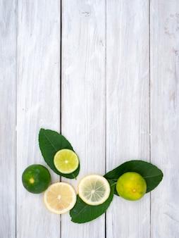 Limão com folhas no fundo de madeira branco