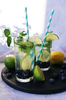 Limão de mirtilo e folhas de hortelã bebem ingredientes para mojito em fundo claro