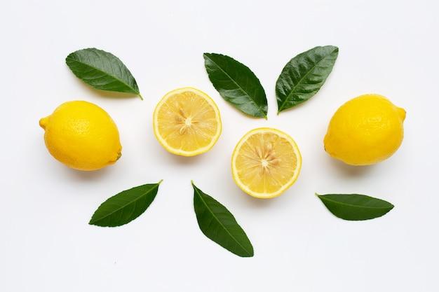 Limão e fatias com as folhas isoladas no branco.