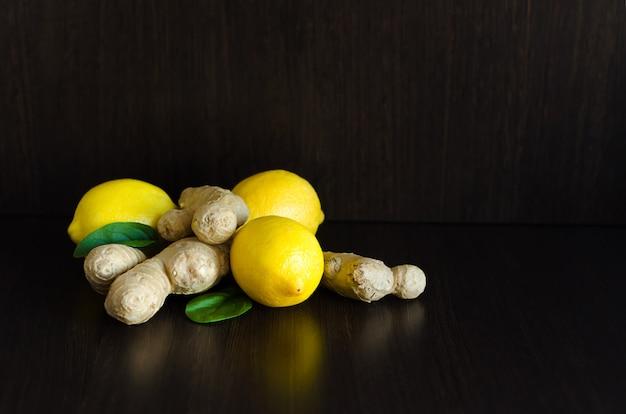 Limão e gengibre para bebidas, estimulando o sistema imunológico no escuro com espaço para texto