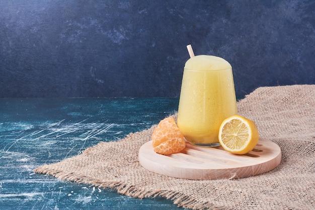 Limão e tangerina com um copo de bebida em azul.