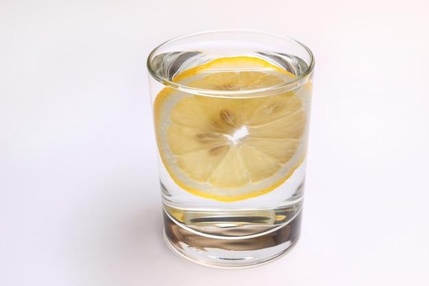Limão em um copo d'água em um fundo branco